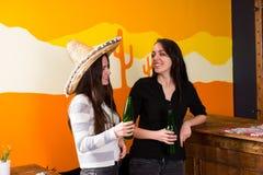 Jeunes femelles de sourire buvant de la bière au compteur de barre Image stock