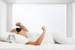 Jeunes femme et horloge d'alarme de sommeil dans la chambre à coucher à la maison images libres de droits