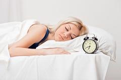 Jeunes femme et horloge d'alarme de sommeil dans la chambre à coucher Photo stock