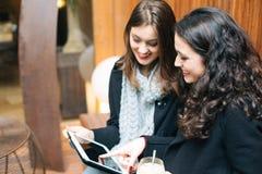 Jeunes femmes à l'aide d'un comprimé dans un café Photos stock