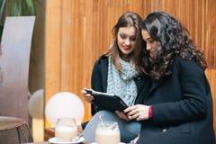 Jeunes femmes à l'aide d'un comprimé dans un café Photos libres de droits