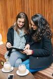 Jeunes femmes à l'aide d'un comprimé dans un café Photo libre de droits