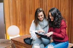 Jeunes femmes à l'aide d'un comprimé dans un café Image libre de droits