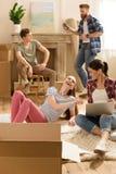 Jeunes femmes à l'aide de l'ordinateur portable sur le tapis tandis qu'amis masculins discutant la relocalisation Photo stock