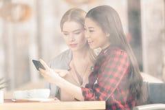Jeunes femmes à l'aide du smartphone tout en buvant du café ensemble lors de la réunion de déjeuner Photographie stock libre de droits