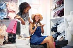 Jeunes femmes à la mode choisissant une paire de chaussures Photos stock
