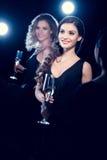 Jeunes femmes élégantes buvant du champagne et passant le temps à la partie Image stock