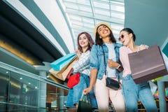 Jeunes femmes élégantes heureuses avec des paniers posant dans le centre commercial Photographie stock libre de droits