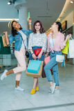 Jeunes femmes élégantes heureuses avec des paniers posant dans le centre commercial Photo stock