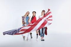 Jeunes femmes élégantes posant avec le drapeau américain dans des mains Photo libre de droits