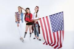 Jeunes femmes élégantes posant avec le drapeau américain dans des mains Photos stock