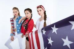 Jeunes femmes élégantes posant avec le drapeau américain dans des mains Images libres de droits