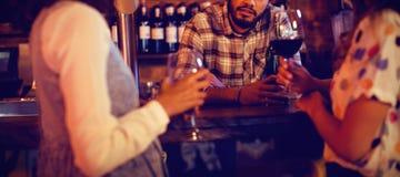 Jeunes femmes agissant l'un sur l'autre avec le barman au compteur photo stock