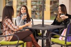 Jeunes femmes appréciant une tasse de café dehors Image stock