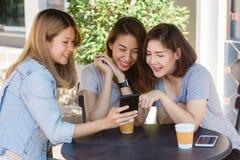 Jeunes femmes asiatiques gaies s'asseyant en café potable de café avec Photo stock