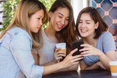 Jeunes femmes asiatiques gaies s'asseyant en café potable de café avec des amis et parlant ensemble Photographie stock