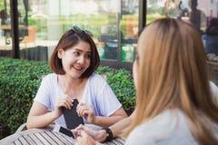 Jeunes femmes asiatiques gaies s'asseyant en café potable de café avec des amis et parlant ensemble Images libres de droits