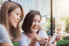 Jeunes femmes asiatiques gaies s'asseyant en café potable de café avec des amis et parlant ensemble Photos libres de droits