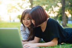 Jeunes femmes asiatiques se trouvant sur l'herbe et employant l'ordinateur portable et la dactylographie Mains de filles sur le c Photographie stock libre de droits