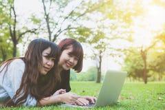 Jeunes femmes asiatiques se trouvant sur l'herbe et employant l'ordinateur portable et la dactylographie Mains de filles sur le c Image stock