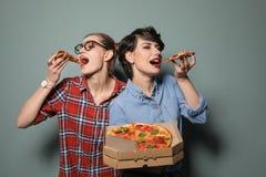 Jeunes femmes attirantes avec la pizza délicieuse Images libres de droits