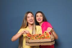 Jeunes femmes attirantes avec la pizza délicieuse Photographie stock libre de droits