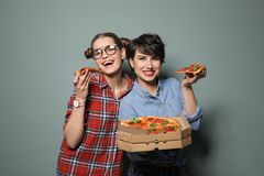 Jeunes femmes attirantes avec la pizza délicieuse sur le fond de couleur Image libre de droits