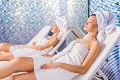 jeunes femmes attirantes détendant sur des lits pliants Images stock