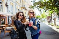 Jeunes femmes attirantes joyeuses drôles de portrait avec des boissons ayant l'amusement sur la rue ensoleillée dans la ville, so Images libres de droits