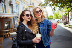 Jeunes femmes attirantes joyeuses drôles de portrait avec des boissons ayant l'amusement sur la rue ensoleillée dans la ville Photos stock