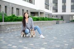 Jeunes femmes attirantes marchant avec le chiot de deux chiens de traîneau sur la rue Photo libre de droits