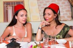 Jeunes femmes attirantes s'asseyant dans le restaurant et le wearin marocains Photo stock