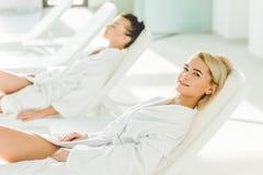 jeunes femmes attirantes se trouvant sur des lits pliants Photo stock