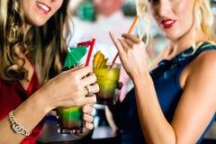 Jeunes femmes avec des cocktails dans le club ou la barre Photographie stock libre de droits