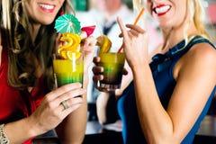 Jeunes femmes avec des cocktails dans le club ou la barre Images libres de droits