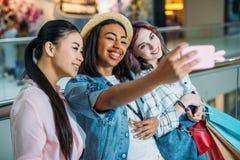Jeunes femmes avec des paniers prenant le selfie, concept de achat de jeunes filles Photos stock