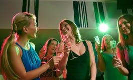 Jeunes femmes avec des verres de champagne dans le club Photo stock