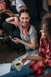 Jeunes femmes avec la tasse de smartphone et de café se souriant Photographie stock libre de droits