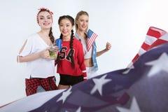 Jeunes femmes avec le drapeau américain regardant l'appareil-photo et buvant des boissons Photo stock