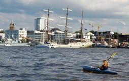 Jeunes femmes avec le kayak devant un bateau de navigation Photographie stock