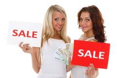 Jeunes femmes avec le signe de vente. Photos libres de droits