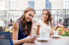 Jeunes femmes avec le smartphone et le café au café Photo stock