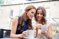 Jeunes femmes avec le smartphone et le café au café Image stock