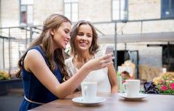 Jeunes femmes avec le smartphone et le café au café Photographie stock