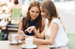 Jeunes femmes avec le smartphone et le café au café Images libres de droits