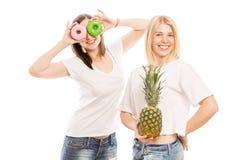 Jeunes femmes avec le sourire d'ananas et de gâteaux photographie stock