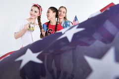 Jeunes femmes avec les boissons potables de drapeau américain d'isolement sur le blanc Image stock