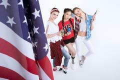 Jeunes femmes avec les boissons potables de drapeau américain d'isolement sur le blanc Photographie stock