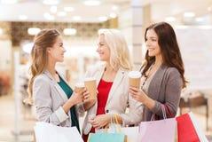 Jeunes femmes avec les paniers et le café dans le mail Photo stock