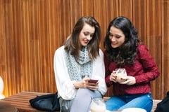 Jeunes femmes avec un mobile dans un café Photos libres de droits